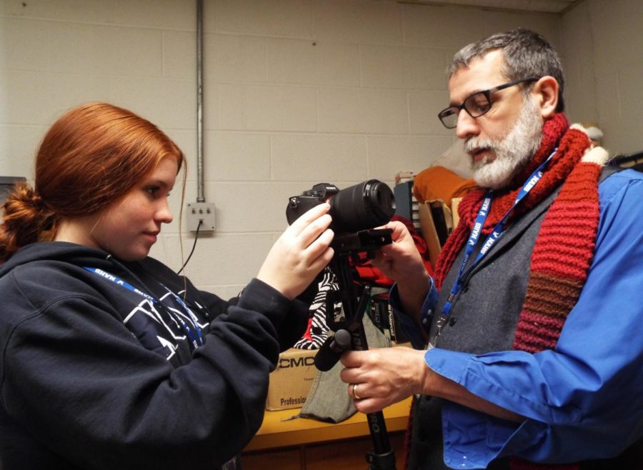 John Doyle (right) works with student Emily Schools, senior, to set up the com-center's new DSLR gliding camera.