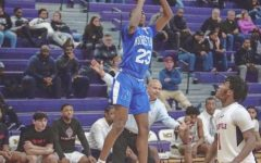 Willie Anderson, 23, launches a jump shot over his defender.